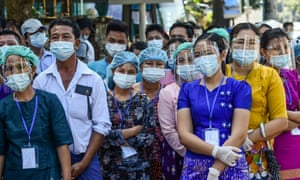 People wearing face shields, face masks and rubber gloves wait to vote at a polling station in Yangon.