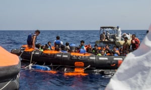 Surviving migrants are brought aboard Irish and Italian navy lifeboats.