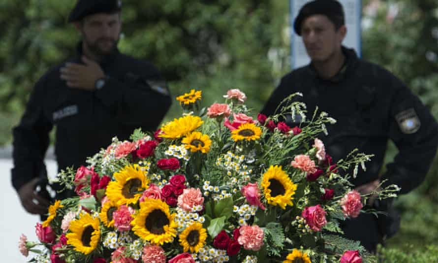 Police officers stand behind a wreath near the Munich shopping centre where the shooting took place.