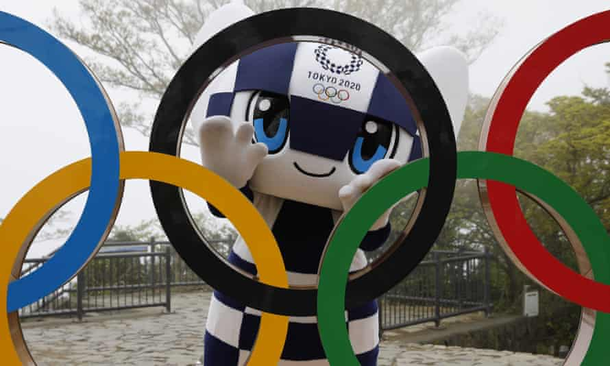 The Tokyo 2020 mascot poses with the Olympic rings.