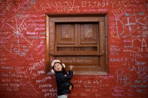Kathmandu, Nepal: A girl looks towards her father as she writes on the wall of a temple
