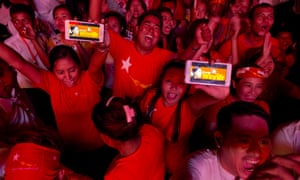 Supporters of Myanmar's National League for Democracy party display their mobile phone with a pictures of Suu Kyi