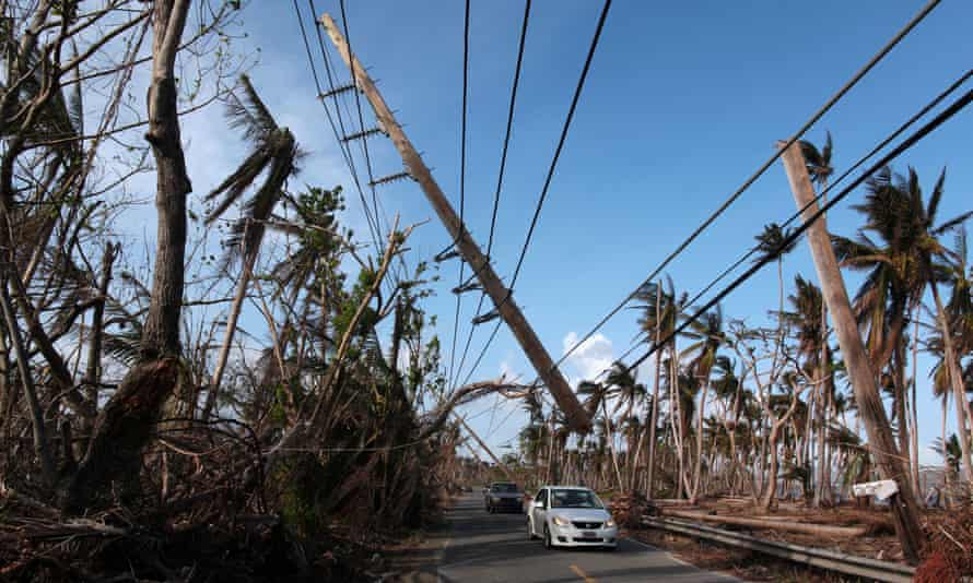Cars drive under a partially collapsed utility pole in Puerto Rico. Nearly three quarters of the island is without electricity.