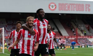 Brentford players celebrate a goal in an empty stadium.