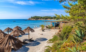 Couple of people walking along Palombaggia beach with restaurant building in background, Corsica island, France