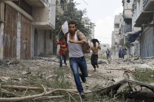 Palestinian men run with a white flag in the Shejaia neighbourhood, which was heavily shelled by Israel during fighting, in Gaza City.<br><br>At least 50 Palestinians were killed by Israeli shelling in the Gaza neighbourhood, and thousands fled for shelter to a hospital packed with wounded,while bodies were unable to be recovered for hours until a brief cease fire was implemented