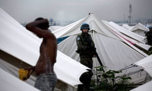 A UN soldier watches a man washing in a refugee camp of Cité Soleil, Port-au-Prince. Sanitation and sewage dispoal was so poor at UN military bases that it 'will potentially damage the reputation of the mission', according to the report.