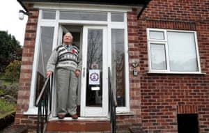 Second world war veteran John Maffey, 93, stands on his doorstep in Knutsford, Cheshire, during the two minutes' silence
