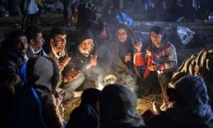 Refugees gather around a fire on the Slovenia-Croatia border on Thursday.