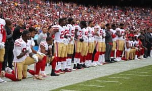 San Francisco 49ers players take a knee during the national anthem prior to their game against  Washington