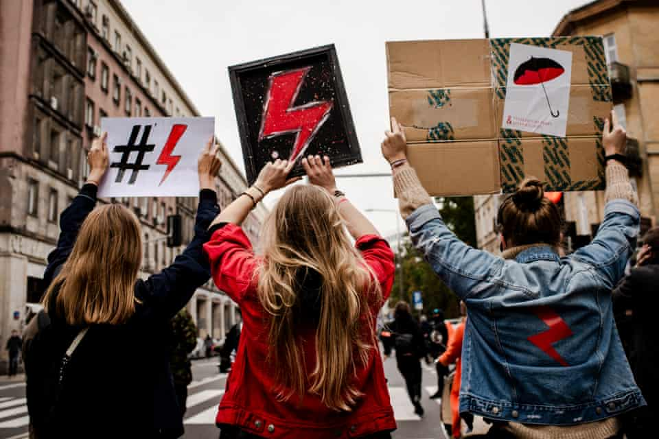 Protesters holding signs during a rally in Warsaw on 27 October.