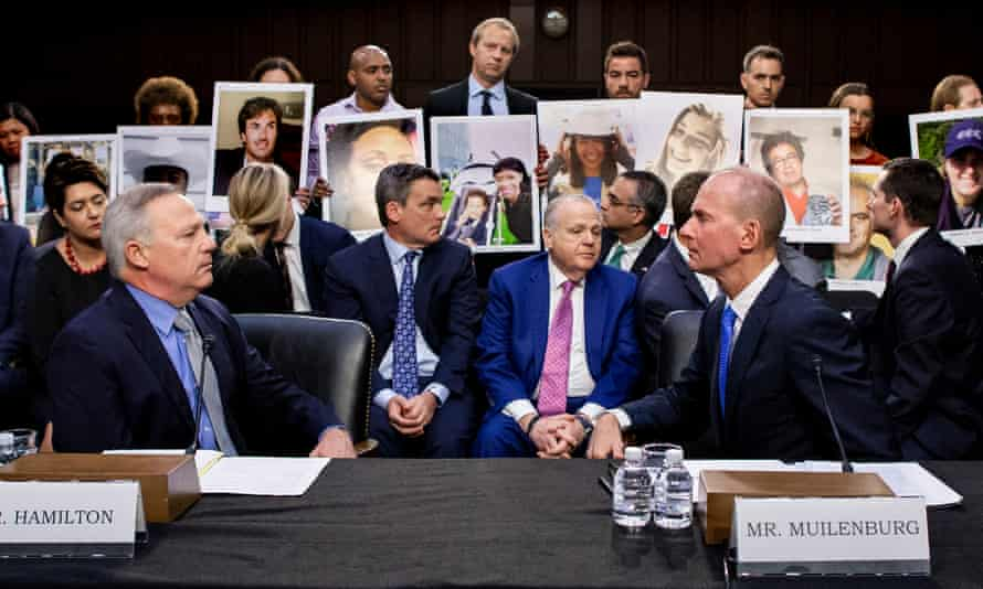 Denis Muilenberg, right, at the hearing in Washington on Wednesday, as family members of the victims who died in the crashes hold pictures of their loved ones.
