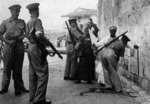 British soldiers searching Arabs for weapons as they enter Jerusalem in 1938.