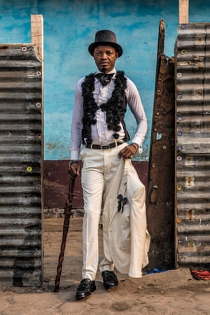 Kass Makenga, 42-year-old clothes seller and sapeur for 20 years, in Brazzaville. Makenga wears a suit and shirt by Christian Berger, waistcoat and hat by Giorgio Armani, walking cane from the Congo and shoes by JM Weston