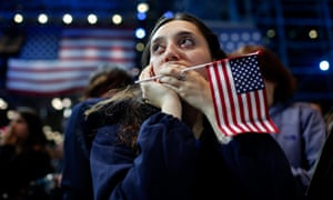 A woman holds an American flag as she watches the US presidential election results