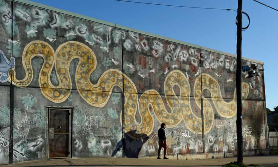 A young man walks past a mural of the rainbow serpent in the NSW town of Bourke