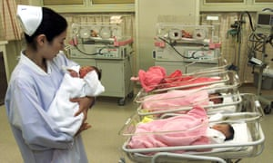 A nurse tends to a newborn child at a hospital in Tokyo