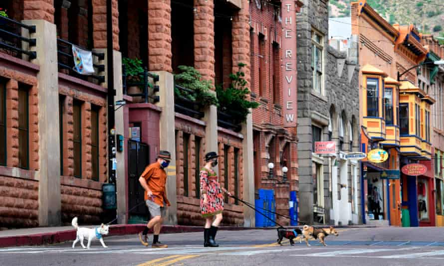 Emily Cayer and Brad Hardy walk their dogs across a quiet Main Street in Bisbee, Arizona.