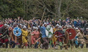 Lots of men in 11th century dress wielding shields spears and swords, in a field