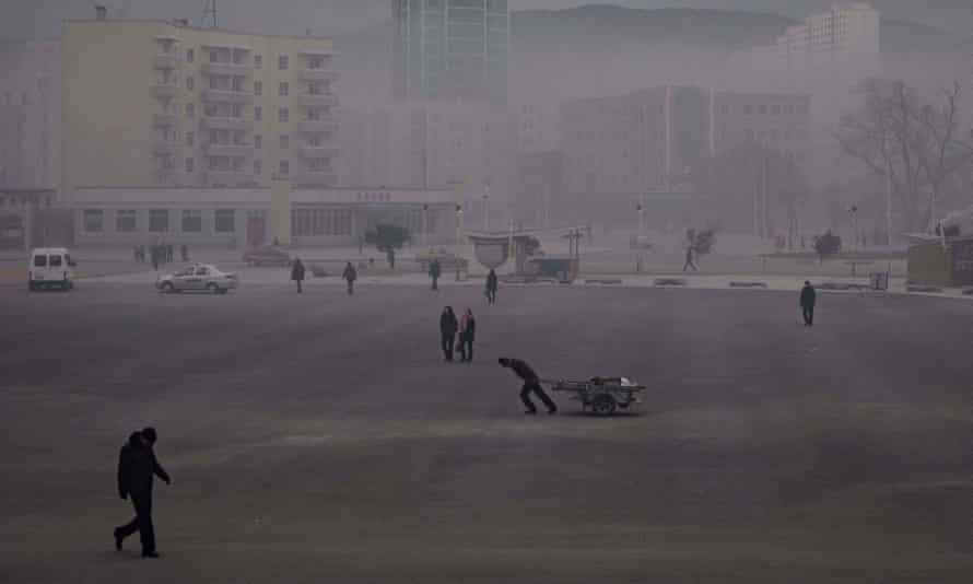 A man drags a cart across a smoggy square in the border city of Rason.