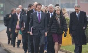 Greg Clark, left, walks with Theresa May and Philip Hammond