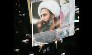 A Saudi anti-government protester carries a poster with the image of jailed Shia cleric Sheik Nimr al-Nimr.