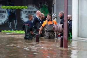 Emergency workers wade through a flooded road on 15 July after heavy rains in Ensival, Belgium. Heavy rain has caused widespread damage and flooding in parts of Belgium