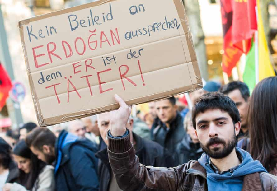 A man holds up a sign that reads 'No offering condolences to Erdogan, since he is the perpetrator'