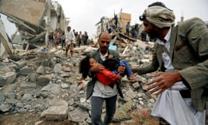A man carries a child from the site of a Saudi-led air strike that killed eight of her family members in Sana'a, Yemen.