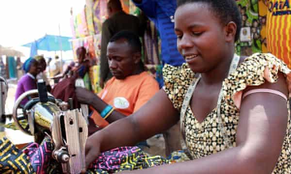 Two tailors from Rwanda and Burundi work at Kityaza market in Nakivale refugee camp.