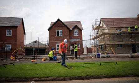 Construction workers build new houses on a housing development on in Middlewich, England.