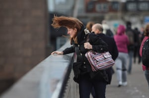 A commuter's hair blows in the wind as they look over the side of London Bridge