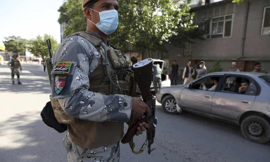 Afghan security personnel search cars at a checkpoint around the Green Zone, which houses embassies, in Kabul