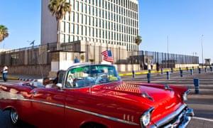 A tourist from California waves a U.S. national flag inside a vintage American car near the U.S. Embassy in Havana, Cuba, on July 20, 2015