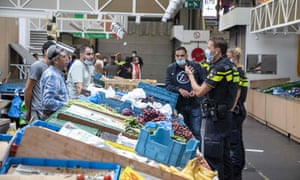 Law enforcers and police clear the De Bazaar Beverwijk, in Beverwijk, The Netherlands, after part of the bazaar was closed by order of the Kennemerland safety department because it appears to be impossible to keep 1.5 metres distance between people to curb the spread of coronavirus.