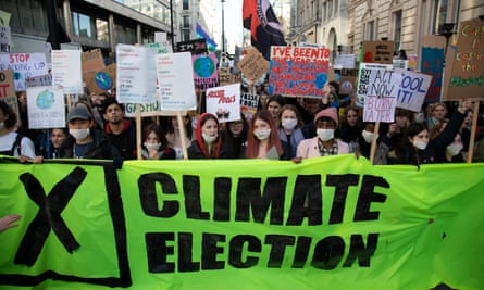 Young protesters gather behind a banner reading 'Climate election' during the Global Climate Strike in London on 29 November 2019.