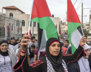 An Arab Israeli woman holds Palestinian flags during the demo.