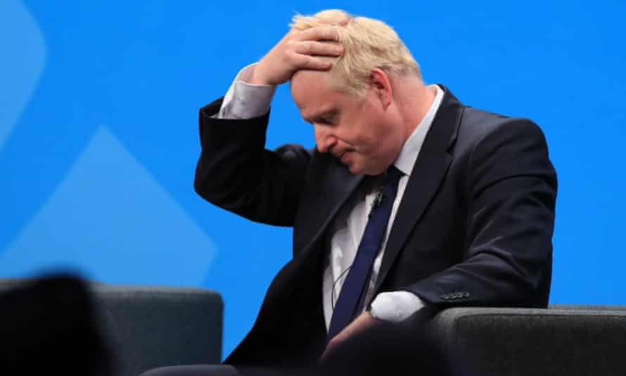 Boris Johnson holds his head in his hands and looks at the floor