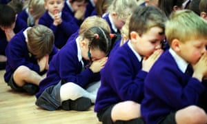 Children pray in a primary school assembly