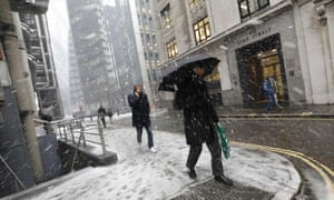 Pedestrians walk through the snow as a blizzard hits central London.