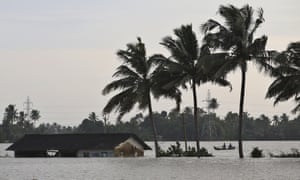 Dois homens remam um barco por um campo de arroz inundado ao lado de uma estrutura inundada em Alappuzha, no estado sulista de Kerala, na Índia.