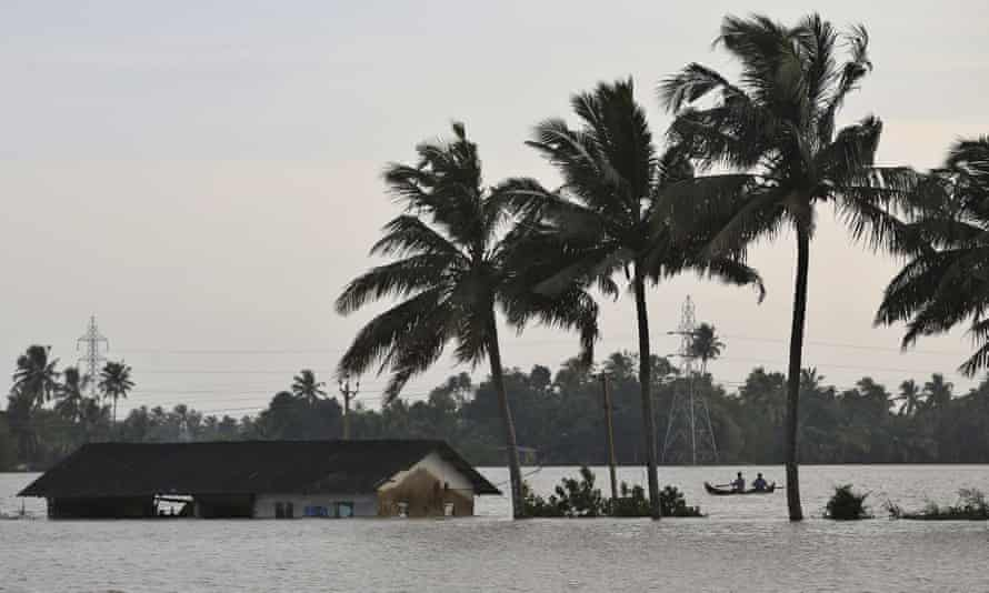 Two men row a boat through a flooded paddy field next to an inundated structure in Alappuzha in the southern state of Kerala, India.