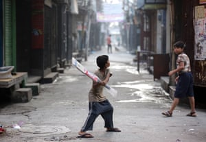 Amritsar, India A child tests his new bat, still wrapped in plastic, as he prepares to go out to play cricket. Cricket is the most popular sport, played and watched, in India