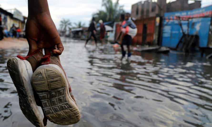 A Congolese man carries his shoes as he wades through floodwaters