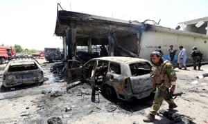 Afghan security forces inspect the site of a suicide attack in Jalalabad