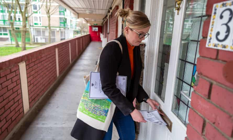 A volunteer posts leaflets for a local community support group through letterboxes on a north London housing estate.