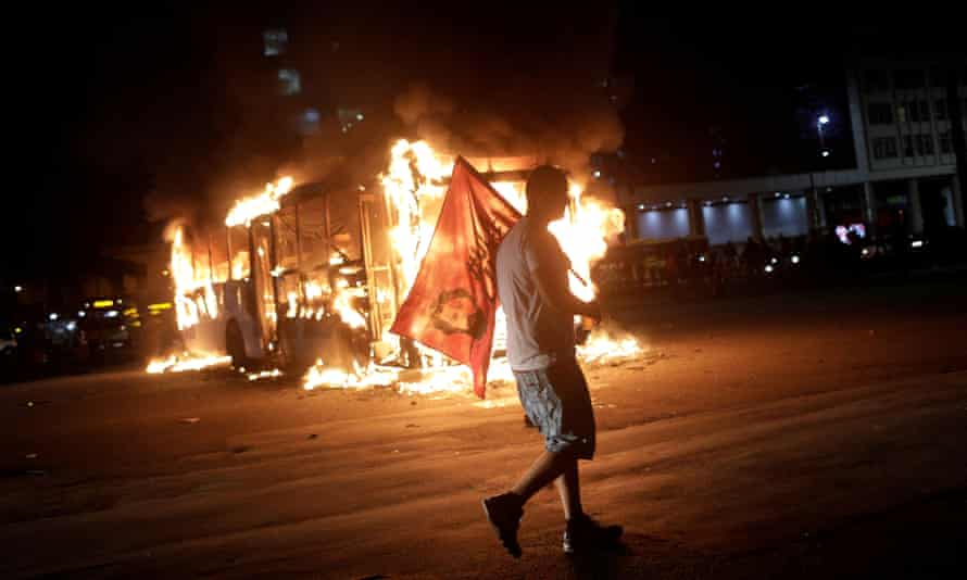 A man carrying a flag with the face of Brazil's former President Lula da Silva walks past a bus set on fire.