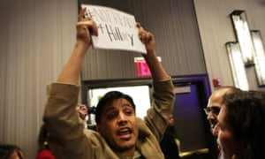 A protester is ushered out as Hillary Clinton speaks at the National Immigrant Integration Conference.