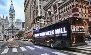 Hundreds of people have rallied in support of Meek Mill at Philadelphia's City Hall, seen in the background.