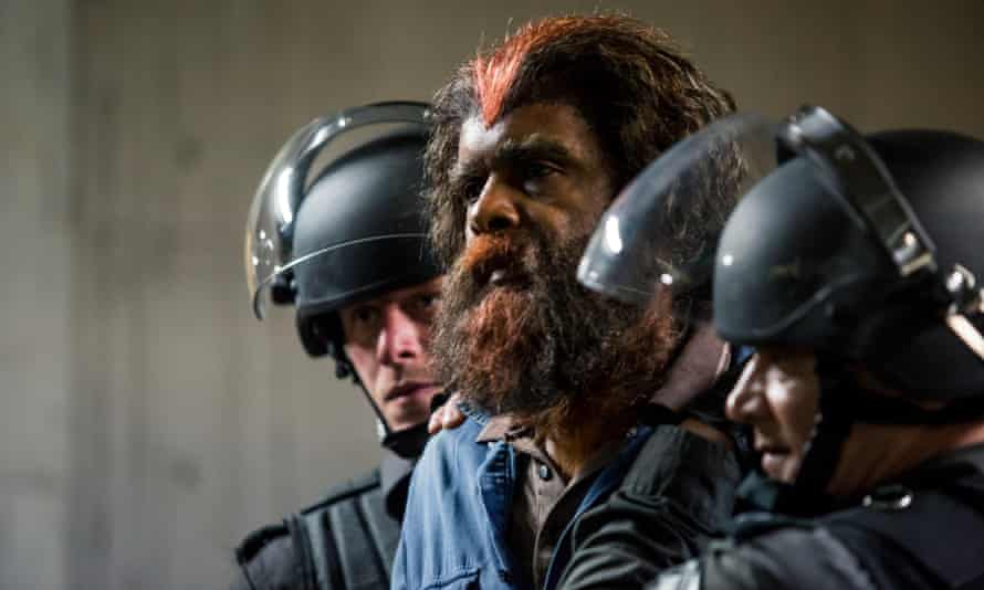 Boondee (Tony Briggs) held by Containment Authority guards.